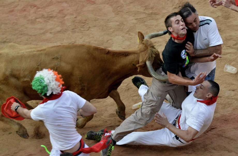 "Revelers are pushed by a bull at the end of last running of the bulls at the San Fermin festival, in Pamplona Spain on Sunday, July 14, 2013. Revelers from around the world arrive to Pamplona every year to take part in some of the eight days of the running of the bulls glorified by Ernest Hemingway's 1926 novel ""The Sun Also Rises."" Photo: AP"