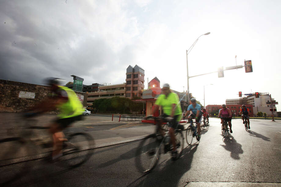 The Cool Cats Cycling Club rides their bikes throughout downtown San Antonio on Monday, July 8, 2013. The club requires its members to wear helmets and have lights on the front and back of their bikes. Photo: Abbey Oldham, San Antonio Express-News / © San Antonio Express-News
