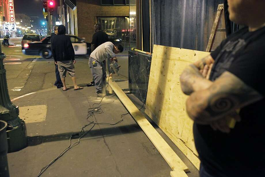 A worker cuts wood to cover the smashed out windows at Dogwood on Telegraph Avenue after protesters set fires and vandalized stores in downtown Oakland, Calif., on Saturday, July 13, 2013, after the acquittal of George Zimmerman in the death of Trayvon Martin earlier in the day. Photo: Carlos Avila Gonzalez, The Chronicle