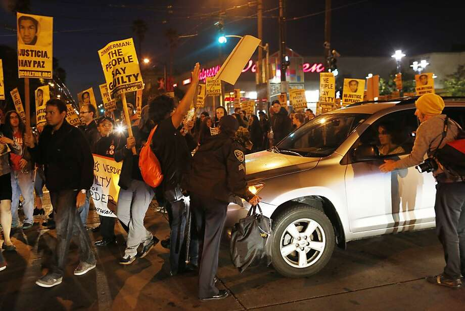 Protestors block an oncoming car on 16th Street during protests in the Mission District after George Zimmerman was found not guilty of the death of Trayvon Martin. Photo: Ian C. Bates, The Chronicle