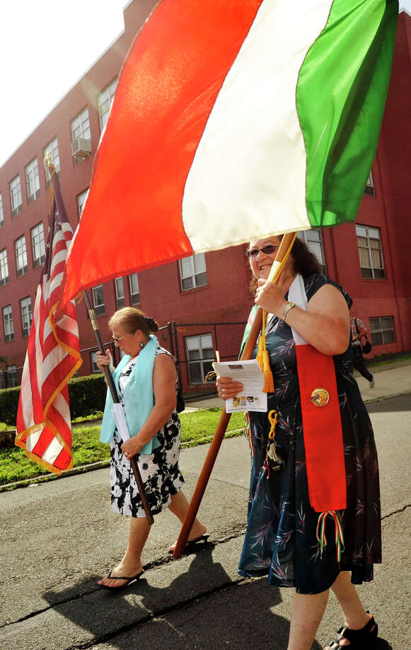 Angela Masone, left, and Teresa Mallozzi carry flags down Schuyler Avenue during the Minturnese community's tenth annual Sagra delle Regne, or harvest festival, procession in Stamford on Sunday, July 14, 2013. The Stamford festival is celebrated simultaneously with its sister city of Minturno, Italy, Photo: Jason Rearick / Stamford Advocate