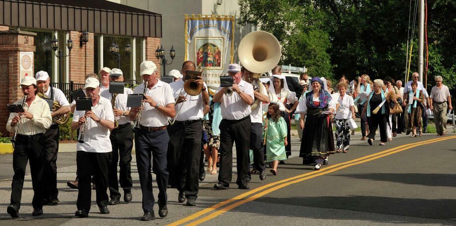 The band leads a group of people down Mill River Street during the Minturnese community's tenth annual Sagra delle Regne, or harvest festival, procession in Stamford on Sunday, July 14, 2013. The Stamford festival is celebrated simultaneously with its sister city of Minturno, Italy, Photo: Jason Rearick / Stamford Advocate