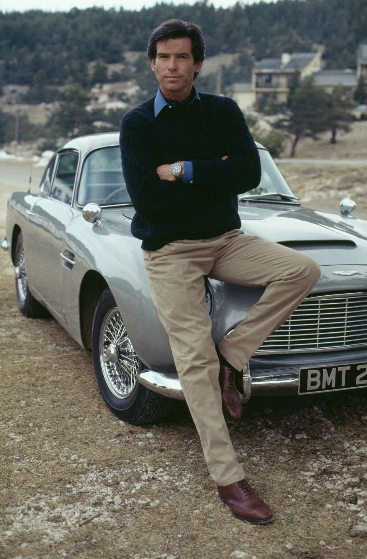 Irish actor Pierce Brosnan poses against an Aston Martin DB5 in a publicity still for the James Bond film 'GoldenEye', 1995.
