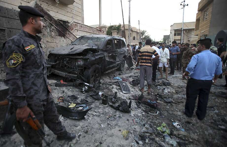 Security forces inspect the scene of a car bomb attack in Basra, 340 miles southeast of Baghdad. A wave of explosions tore through overwhelmingly Shiite areas around the country. Photo: Nabil Al-Jurani, Associated Press