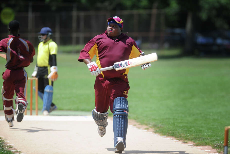 Batsman Kenneth Pierre, of Stratford, a player for the Bridgeport Cricket Club, runs between the wickets during his team's match with the Cheshire Cricket Club at Newfield Park in Bridgeport, Conn on Sunday, July 14, 2013. Photo: Brian A. Pounds / Connecticut Post