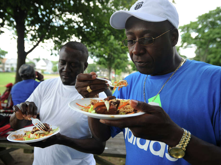 Derrick Marshall, left, and Rowan Brown, both of Bridgeport, eat Jamaican food during the cricket match at Newfield Park in Bridgeport, Conn on Sunday, July 14, 2013. Photo: Brian A. Pounds / Connecticut Post