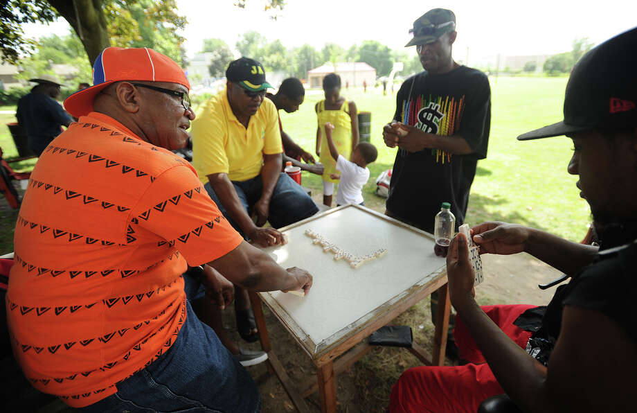 From left; Lynoval Allen, Lloyd Reid, O'Neil Wilson, and Gerry Genus, all of Bridgeport, play the popular Jamaican game of dominoes at the cricket match between the Bridgeport Cricket Club and the Cheshire Cricket Club at Newfield Park in Bridgeport, Conn on Sunday, July 14, 2013. Photo: Brian A. Pounds / Connecticut Post