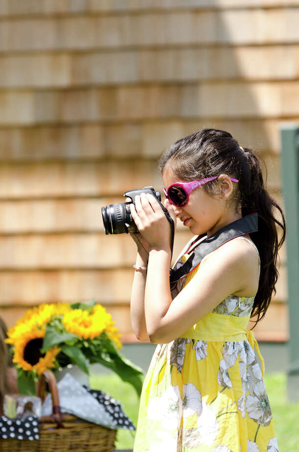 Kashvi Kumar, 10, of Westport, takes a photo during the first annual Virginia House of Hope charity polo match fundraiser at the Greenwich Polo Club at Conyers Farm on Hurlingham Drive in Greenwich on Sunday, July 14, 2013. Photo: Amy Mortensen / Connecticut Post Freelance