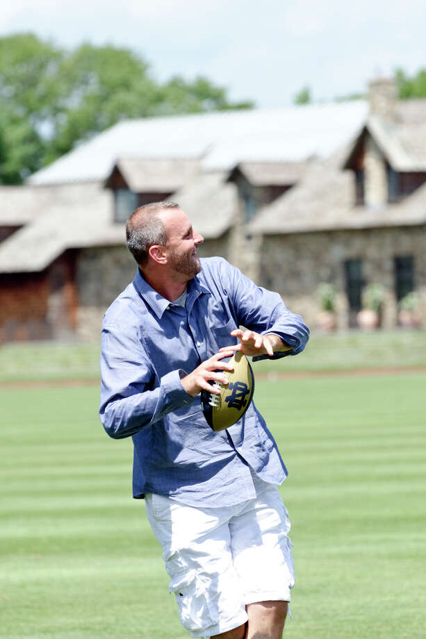 Jay Chalnick, of Greenwich, throws a football during the first annual Virginia House of Hope charity polo match fundraiser at the Greenwich Polo Club at Conyers Farm on Hurlingham Drive in Greenwich on Sunday, July 14, 2013. Photo: Amy Mortensen / Connecticut Post Freelance