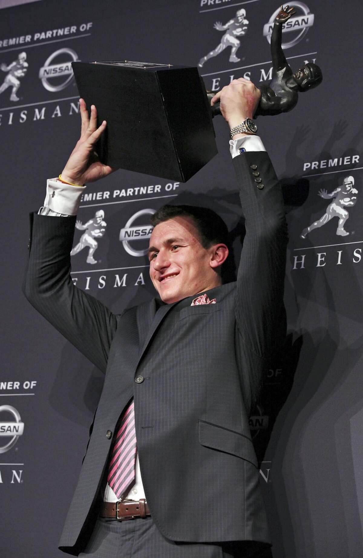 Texas A&M's quarterback Johnny Manziel, the 2012 Heisman Trophy winner, poses for photos during a press conference Saturday Dec. 8, 2012 at the New York Marriott Marquis hotel in New York, New York.