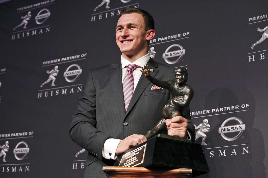 Texas A&M's quarterback Johnny Manziel, the 2012 Heisman Trophy winner, poses for photos during a press conference Saturday Dec. 8, 2012 at the New York Marriott Marquis hotel in New York, New York. Photo: Edward A. Ornelas, San Antonio Express-News
