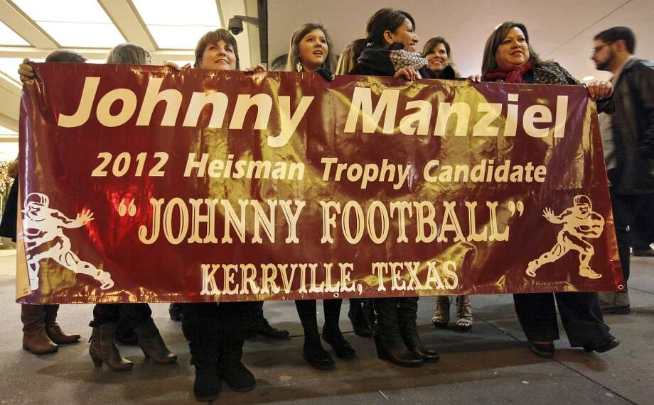 Fans from Kerrville, Tx., hold a sign for Heisman finalist Texas A&M's quarterback Johnny Manziel outside the New York Marriott Marquis hotel before the Heisman winner announcement Saturday Dec. 8, 2012 in New York, New York. Photo: Edward A. Ornelas, San Antonio Express-News