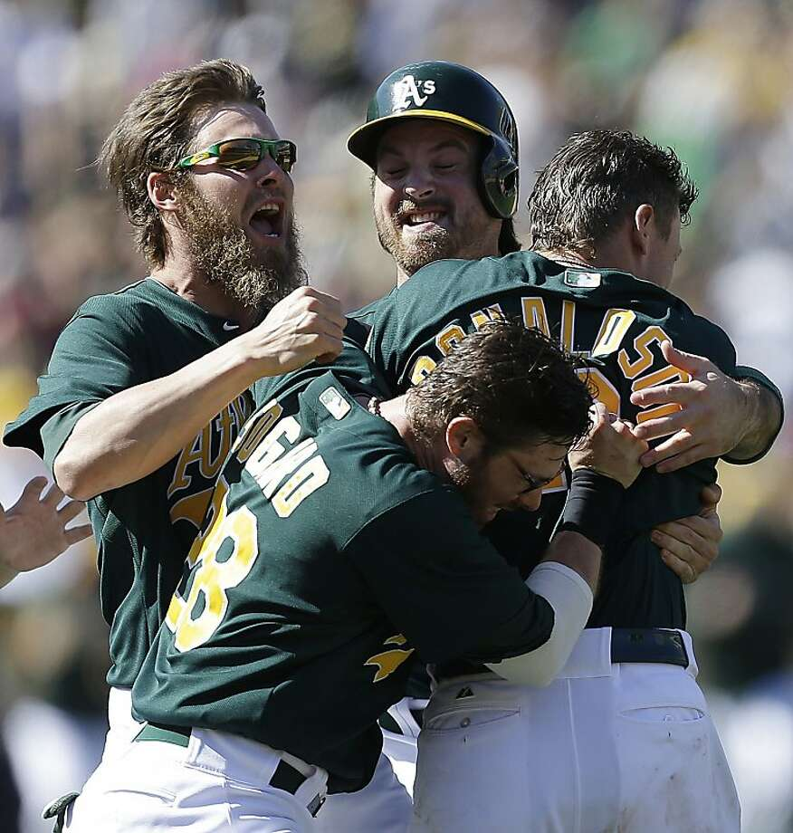 Josh Donaldson gets mobbed by his teammates after his 11th-inning single gave the A's a 3-2 victory. Photo: Ben Margot, Associated Press