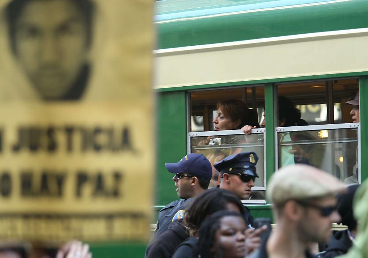 Muni riders look out the window as protesters march on Market St. during a rally denouncing the not guilty verdict in the George Zimmerman murder trial in San Francisco on Sunday, July 14, 2013.