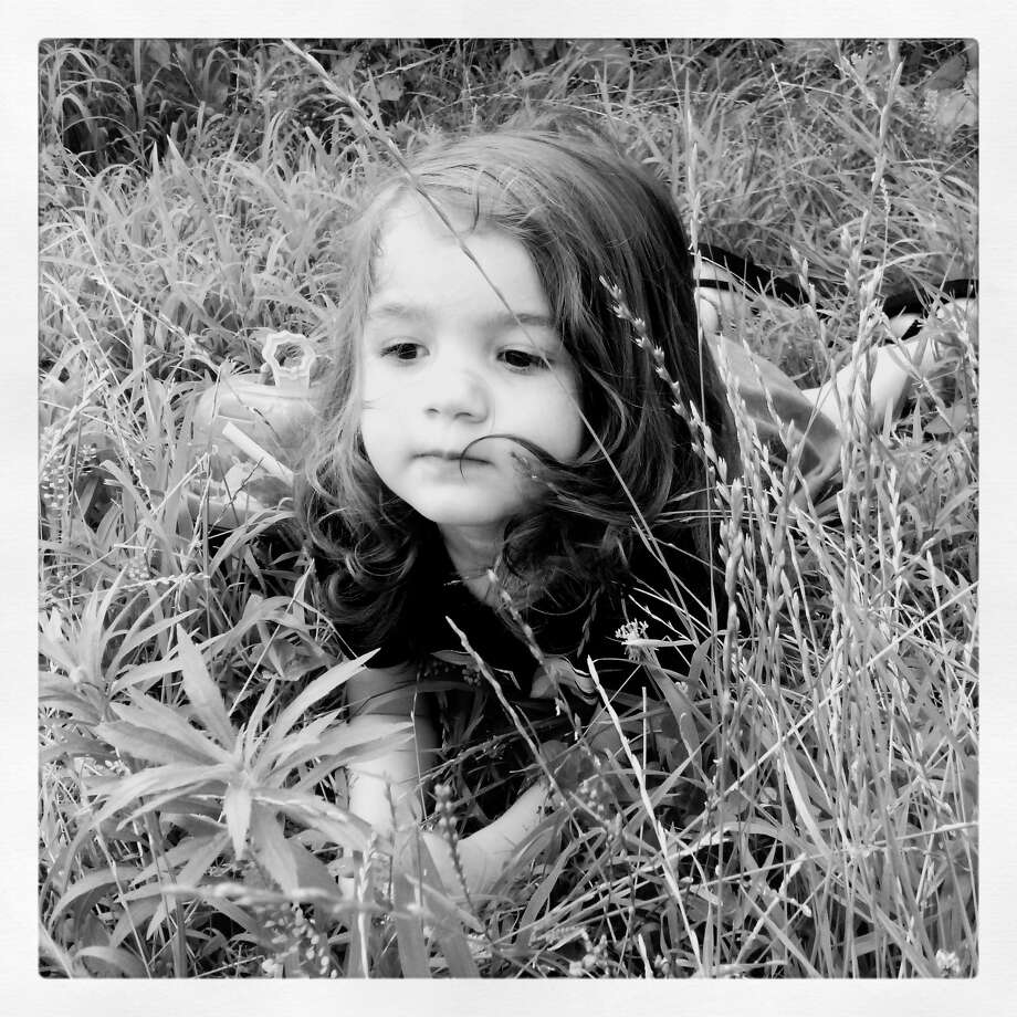 Laura Dingman's daughter Evangeline lays in the grass at their Troy home after running around and blowing bubbles. (Laura Dingman)