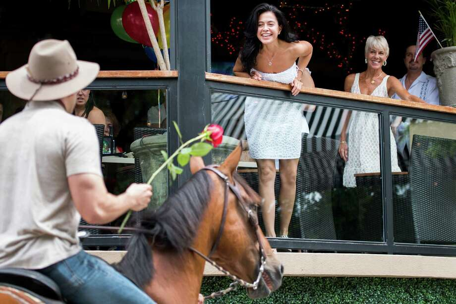 Jennifer Ann Molleda leans over the railing of the Monarch Restaurant the Hotel ZaZa to accept a rose from her boyfriend Alan Wakim, who rode up to the balcony on horseback to propose marriage. Photo: Smiley N. Pool, Houston Chronicle / © 2013  Houston Chronicle