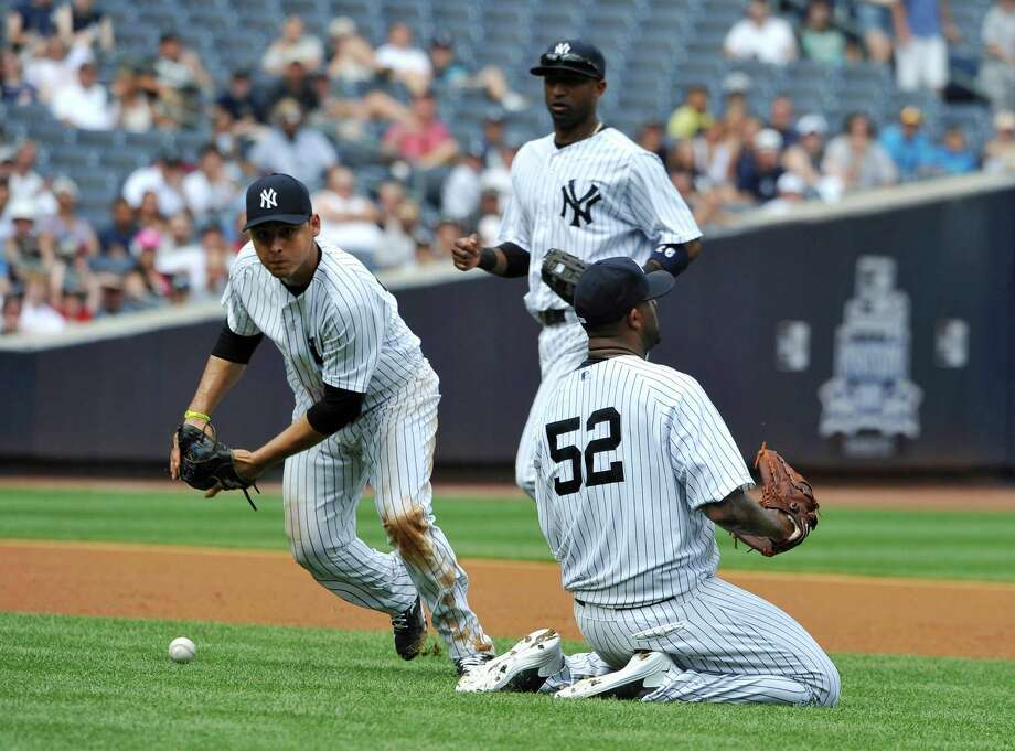 New York Yankees third baseman Luis Cruz, left,  shortstop Eduardo Nunez, center, and starting pitcher CC Sabathia, right, can't field a single hit by Minnesota Twins' Justin Morneau allowing a run to score in the fourth inning of a baseball game at Yankee Stadium on Sunday, July 14, 2013 in New York. (AP Photo/Kathy Kmonicek) ORG XMIT: NYY107 Photo: Kathy Kmonicek / FR170189 AP
