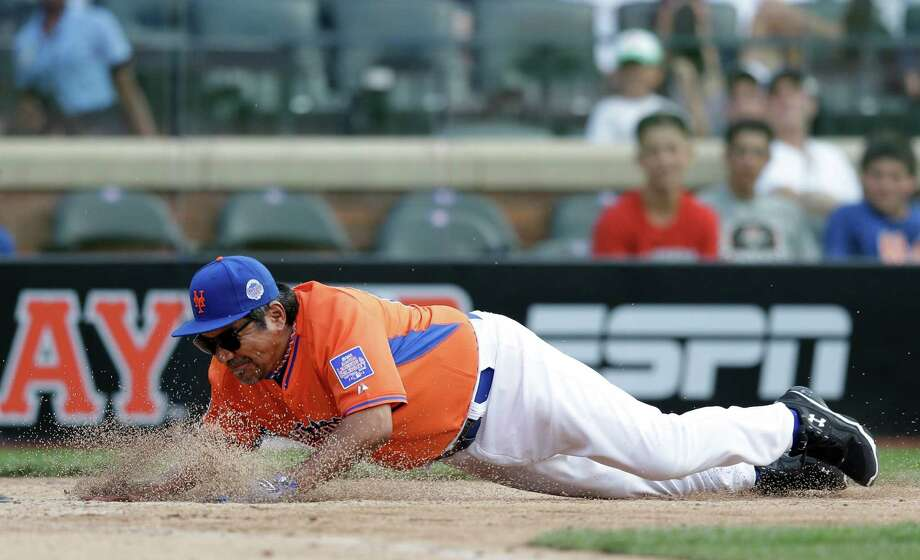 Comedian George Lopez, representing the National League, slides into home plate during the All Star Legends & Celebrity Softball Game on Sunday, July 14, 2013 in New York. Photo: AP
