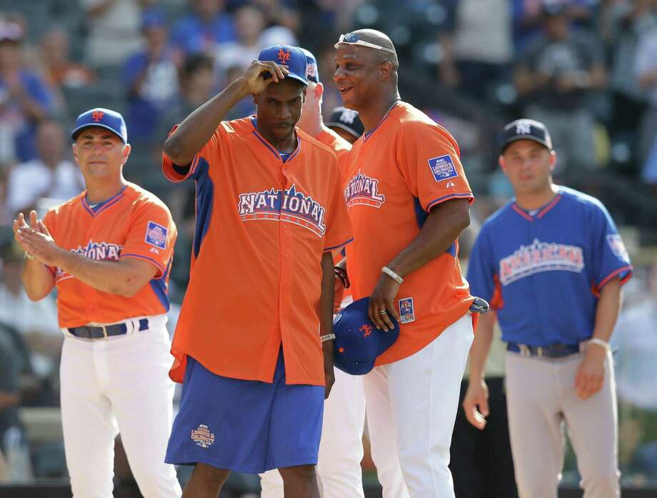 Former New York Mets players Dwight Gooden, second from left, and Darryl Strawberry, second from right, are greeted at the start of the All Star Legends & Celebrity Softball Game on Sunday, July 14, 2013 in New York. Photo: AP