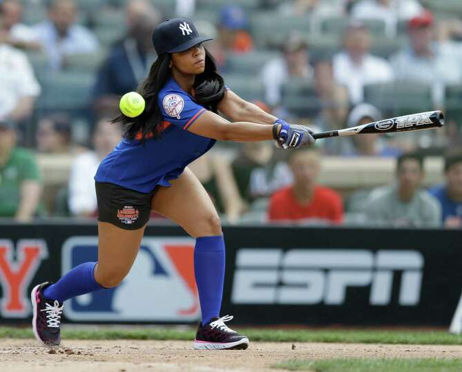 Singer Ashanti swings at a pitch during the All Star Legends & Celebrity Softball Game on Sunday, Ju