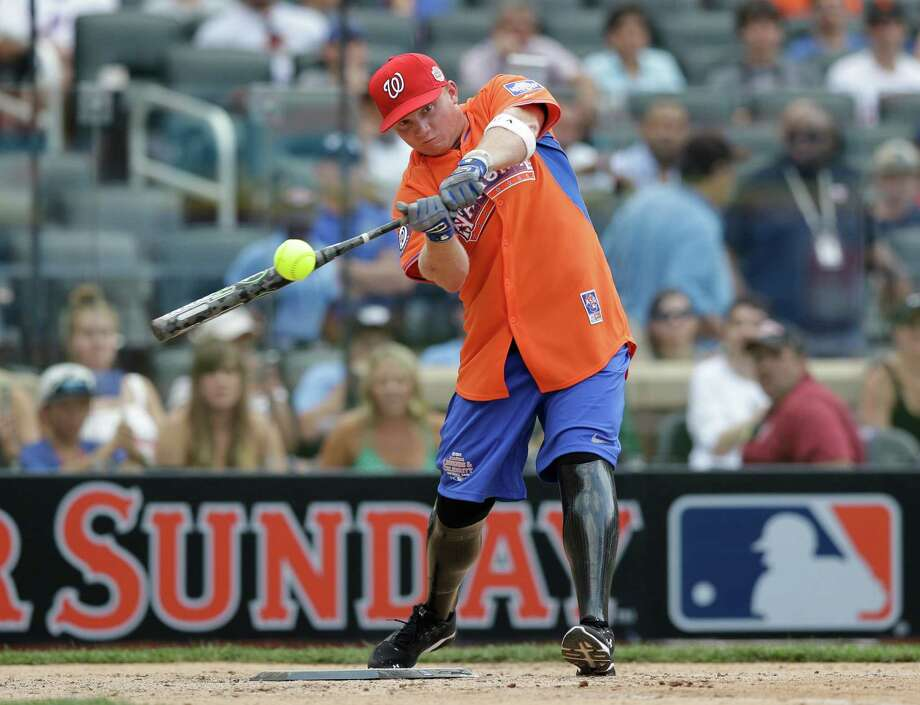 Wounded Warrior Josh Wege swing at a pitch during the All Star Legends & Celebrity Softball Game on Sunday, July 14, 2013 in New York. Photo: AP