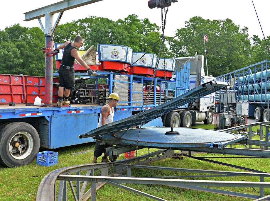Ethan Lightfoot, left, of Phoenix, Ariz., and Anthony Alexander of Durham, S.C., set up the Tilt-A-Whirl ride Thursday morning, July 11, 2013, at the Saratoga County Fairgrounds in Ballston Spa, N.Y.   The fair opens July 16.  (John Carl D'Annibale / Times Union) Photo: John Carl D'Annibale / 10023108A