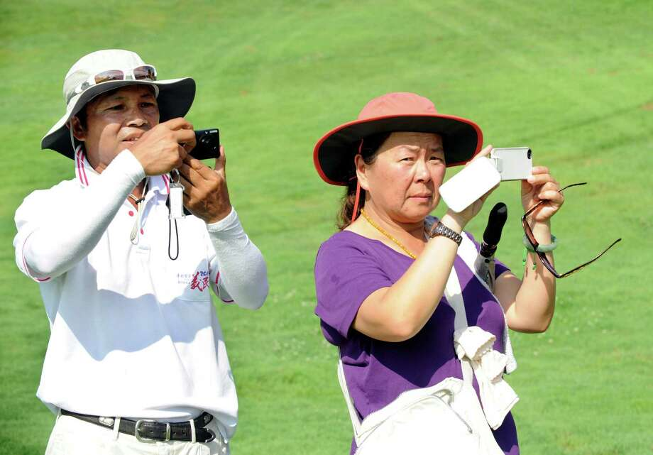Chen-Min Hsu and his wife  photograph their daughter Wei-Ling Hsu after  winning the final round of the Credit Union Challenge on the Symetra Tour stop held at Capital Hills golf course in Albany, N.Y., Sunday, July 14, 2013. (Hans Pennink / Special to the Times Union) ORG XMIT: HP116 Photo: Hans Pennink / Hans Pennink