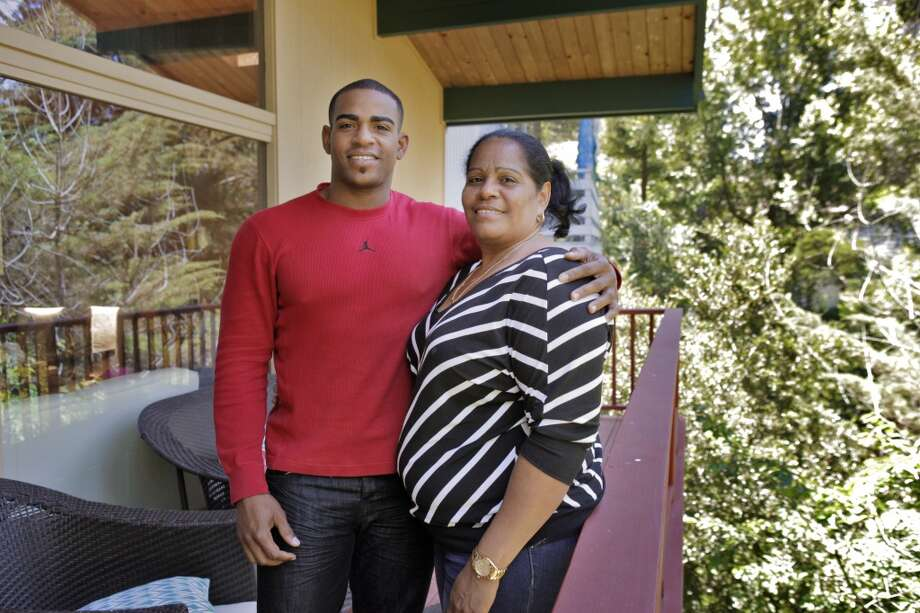 Yoenis Cespedes, of the Oakland Athletics, with his mother Estela Milanes at his home in the Oakland hills on Friday, May 31, 2013, in Oakland, Calif. The family was finally reunited after they spent nearly a year and a half apart while Yoenis's mother and cousins struggled to travel from one Carribean island to another.