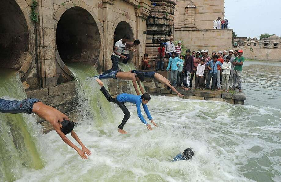 TOPSHOTS Indian Muslim youth dive as flood waters enter the tank of the 600 year old Sarkhej Roza architectural complex, which has been dry for the last seven years, in Ahmedabad on July 14, 2013.  The Sarkhej Roza is maintained by the Archeological Survey of India and this tomb and mosque of a Sufi saint are known in this region as 'Ganj Bakhsh'.  AFP PHOTO / Sam PANTHAKYSAM PANTHAKY/AFP/Getty Images Photo: Sam Panthaky, AFP/Getty Images