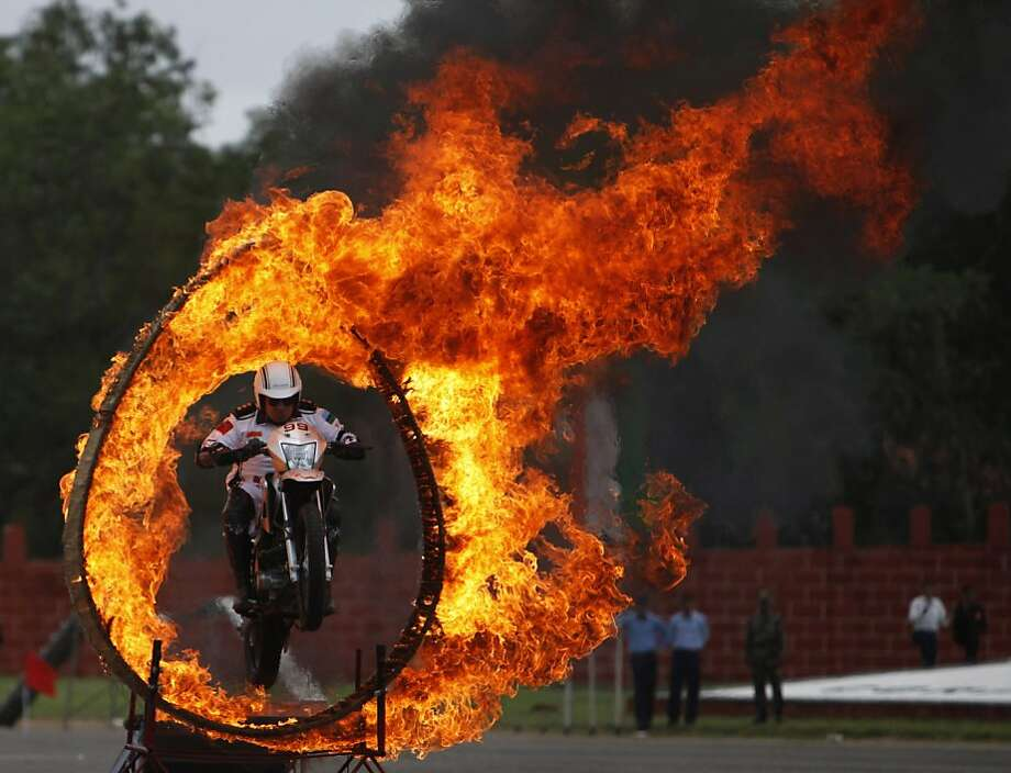 An Indian army soldier on a motorcycle performs a stunt during a display held as part of the sixtieth anniversary celebrations of the Military College of Electronics and Engineering in Hyderabad, India, Sunday, July 14, 2013. (AP Photo/Mahesh Kumar A.) Photo: Mahesh Kumar A, Associated Press