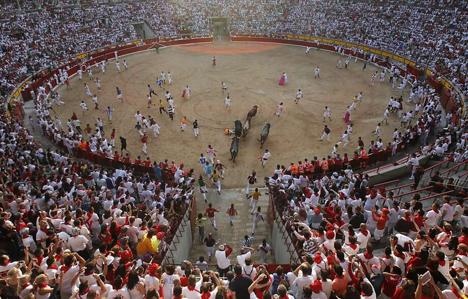 "Runners enter the bullring followed by ""Miura"" fighting bulls during the final running of the bulls at the San Fermin festival, in Pamplona, Spain, Sunday, July 14, 2013. Revelers from around the world arrive to Pamplona every year to take part in some of the eight days of the running of the bulls glorified by Ernest Hemingway's 1926 novel ""The Sun Also Rises."" (AP Photo/Alvaro Barrientos) Photo: Alvaro Barrientos, Associated Press"