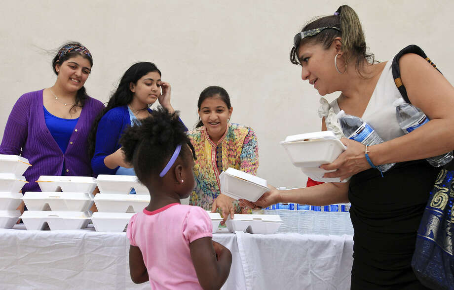 Shaya Kara, 18, (from left rear), her sister Tabreez Kara, 13, and Sakina Tajkhanji, 15, distribute food to Haven for Hope members Namine' Jones, 4, and Christine Vargas before the 