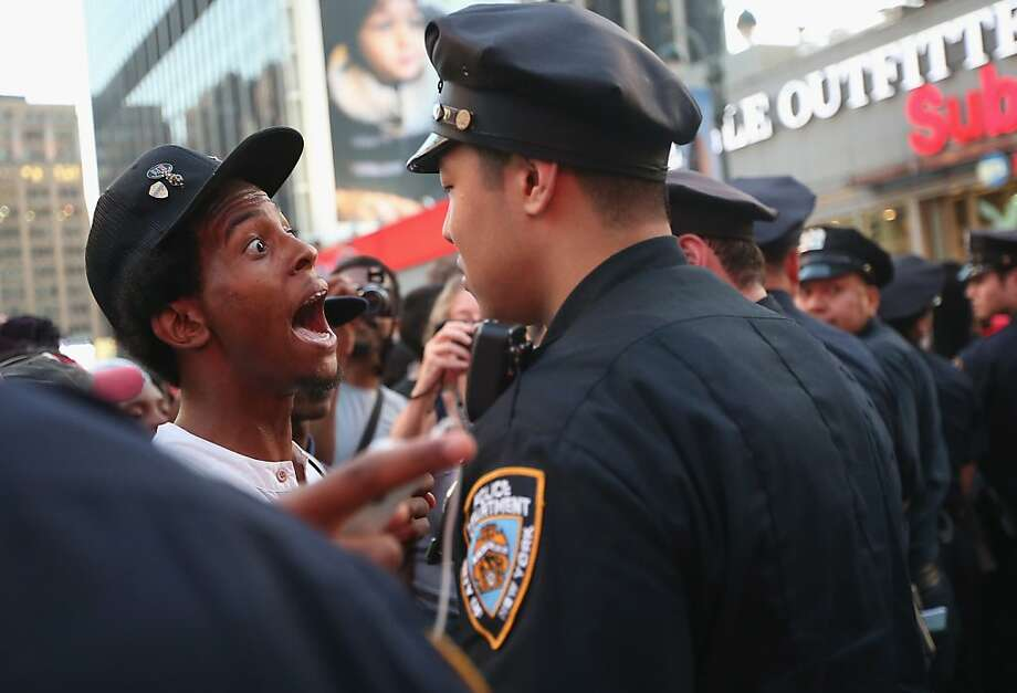 NEW YORK, NY - JULY 14:  A man argues with a police officer as Trayvon Martin supporters march while blocking traffic after a rally for Martin in Union Square in Manhattan on July 14, 2013 in New York City. George Zimmerman was acquitted of all charges in the shooting death of Martin July 13 and many protesters questioned the verdict.  (Photo by Mario Tama/Getty Images) Photo: Mario Tama, Getty Images