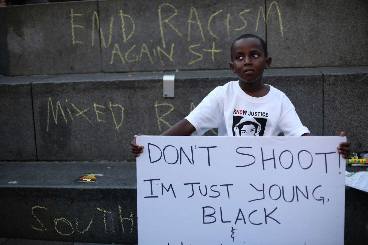 Abdul Kebbeh, 6, holds a sign at Westlake Park on Sunday, July 14, 2013 in downtown Seattle. Hundreds of people gathered at Westlake and marched to the Federal Courthouse to protest the acquittal of George Zimmerman, the Florida man that shot and killed Trayvon Martin.
