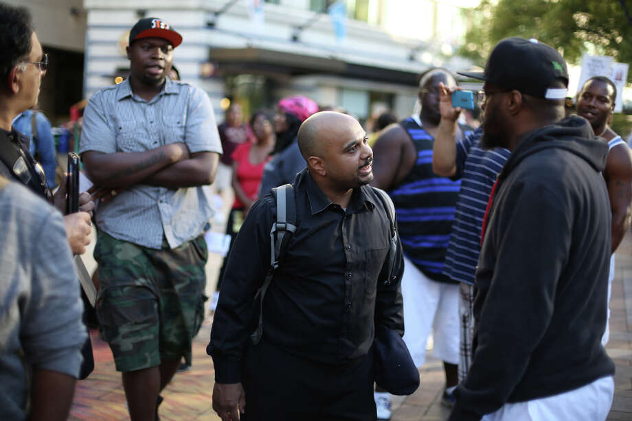 J. Boswell, center, confronts other protesters, asking how they could make this a black and white issue. Boswell, who said he is of mixed race, said he has experienced racial issues from multiple perspectives. Boswell was involved in a few brief shouting matches with protesters during the rally. Photo: JOSHUA TRUJILLO, SEATTLEPI.COM
