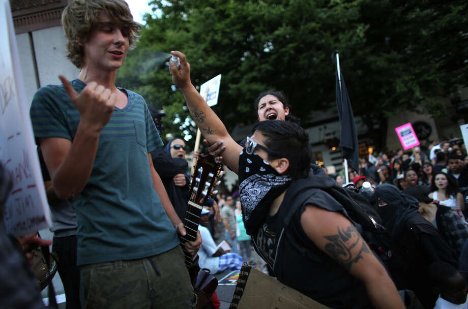 Musician Andrew Anderson is sprayed in the face with a foul smelling chemical as he was about to play a song on the stage at Westlake Park. Black-clad protesters were upset that marchers returned to the park. The protesters, including the one seen spraying the chemical here, wanted to continue marching. Photo: JOSHUA TRUJILLO, SEATTLEPI.COM