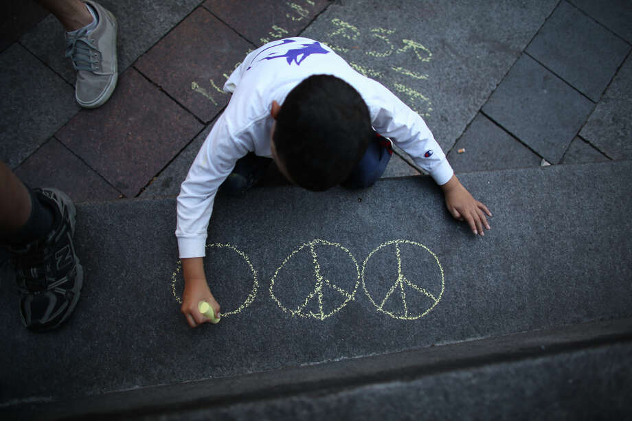 A young boy draws peace signs at Westlake Park on Sunday in downtown Seattle. Hundreds of people gathered at Westlake and marched to the Federal Courthouse to protest the acquittal of George Zimmerman, the Florida man that shot and killed Trayvon Martin. Photo: JOSHUA TRUJILLO, SEATTLEPI.COM