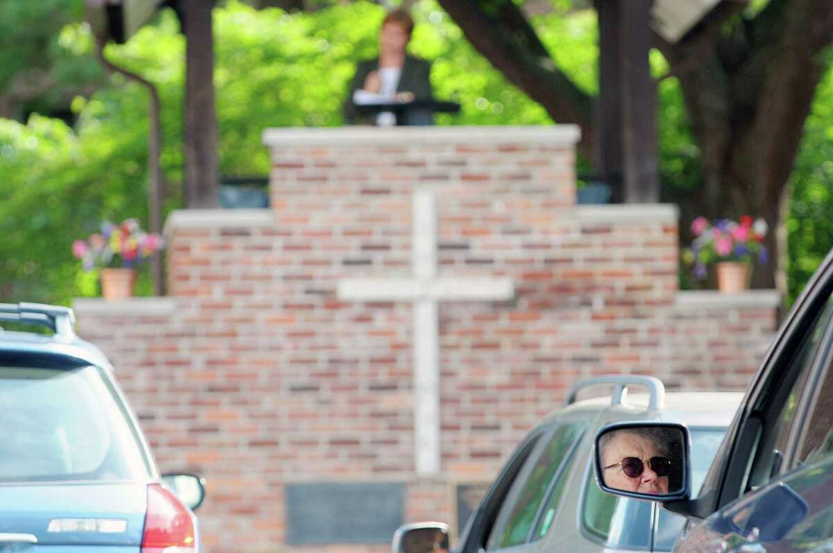 Parishioner, Janet Conti, is reflected in her vehicle's side mirror as the Rev. Susan Vincent-Cox holds service during the First Church in Albany Drive-In Worship service on Sunday, July 14, 2013 in Albany, NY. The church holds an outdoor service at 9am on Sundays in the summer months. (Paul Buckowski / Times Union)