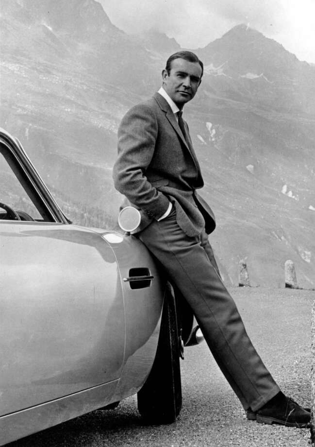 Take a look back at Aston Martin over the past 100 years, before the age of electric cars. 1964:  Actor Sean Connery poses as James bond next to his Aston Martin DB5 in a scene from the United Artists release 'Goldfinger' in 1964  Photo by Michael Ochs Archives/Getty Images Photo: Michael Ochs Archives, Getty Images / Michael Ochs Archives