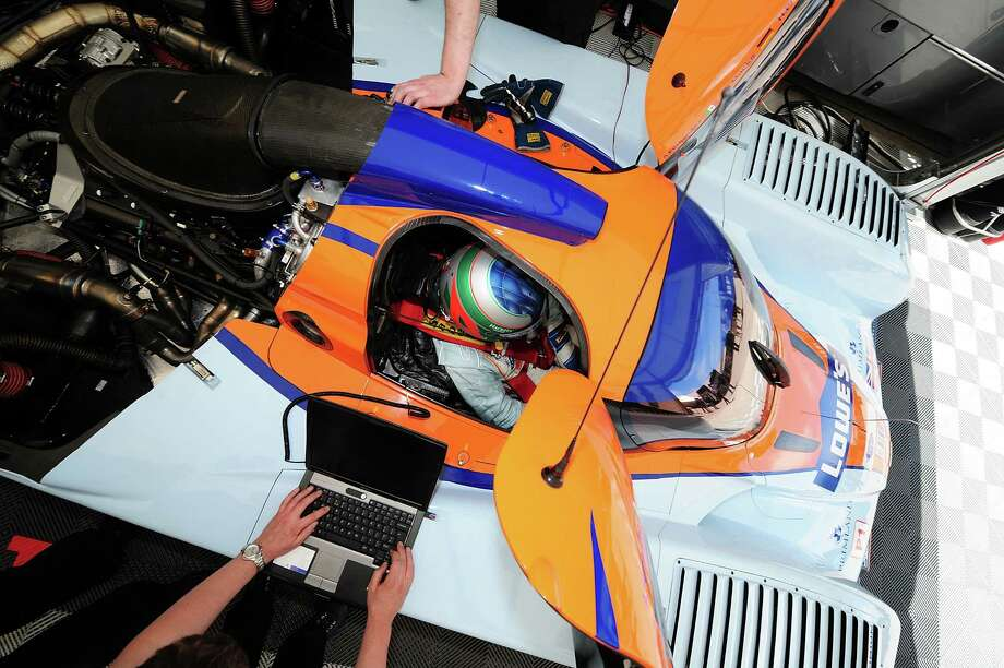 Adrian Fernandez of Mexico sits in the # 007 Aston Martin prototype while the crew makes repairs during practice for the ALMS 12 Hours of Sebring at Sebring International Raceway,  March 18,  2010 in Sebring, Florida. Photo: Rick Dole, Getty Images / 2010 Rick Dole