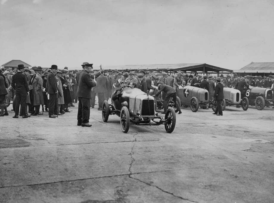 1922:  Motor racing at Brooklands, Weybridge, Surrey, cars leaving paddock for a race. Centre is Lionel Martin in a Aston Martin and car No4 is a 11.9 h.p Lagonda (69 x 100mm :1,496cc). Photo: Topical Press Agency, Getty Images / Hulton Archive