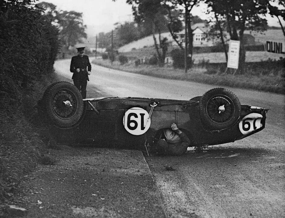 6th September 1935:  A racing car driver emerges from a crash, his car having overturned. Photo: Fox Photos, Getty Images / Hulton Archive