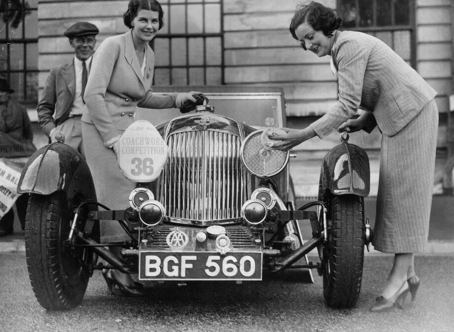 21st July 1935:  Two women polish their Aston Martin sports car before the start of the coachwork competition held in connection with the Welsh Motor Rally being held in Cardiff. Photo: Richards, Getty Images / Hulton Archive