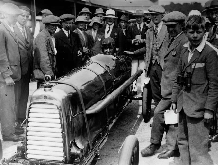 August 1923:  Major Halford in a Razor-Blade Aston Martin at a Brooklands meeting surrounded by fans. Photo: Topical Press Agency, Getty Images / Hulton Archive