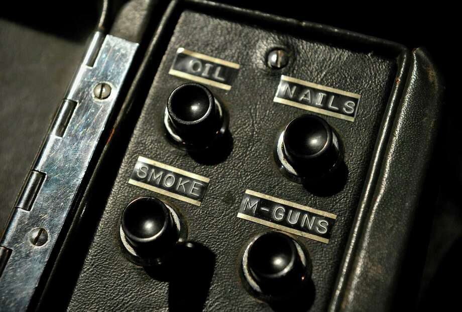 Gadget switches are pictured inside a 1964 Aston Martin DB5 vehicle used by British actor Sean Connery when he played fictional spy charachter James Bond in the films 'Goldfinger' and 'Thunderball,' during a photocall in London, on October 27, 2010. James Bond's famous Aston Martin car was expected to raise over five million dollars when it goes on sale later Wednesday, complete with gadgets including ejector seat and revolving number plates. AFP PHOTO/CARL COURT Photo: CARL COURT, Getty Images / 2010 AFP