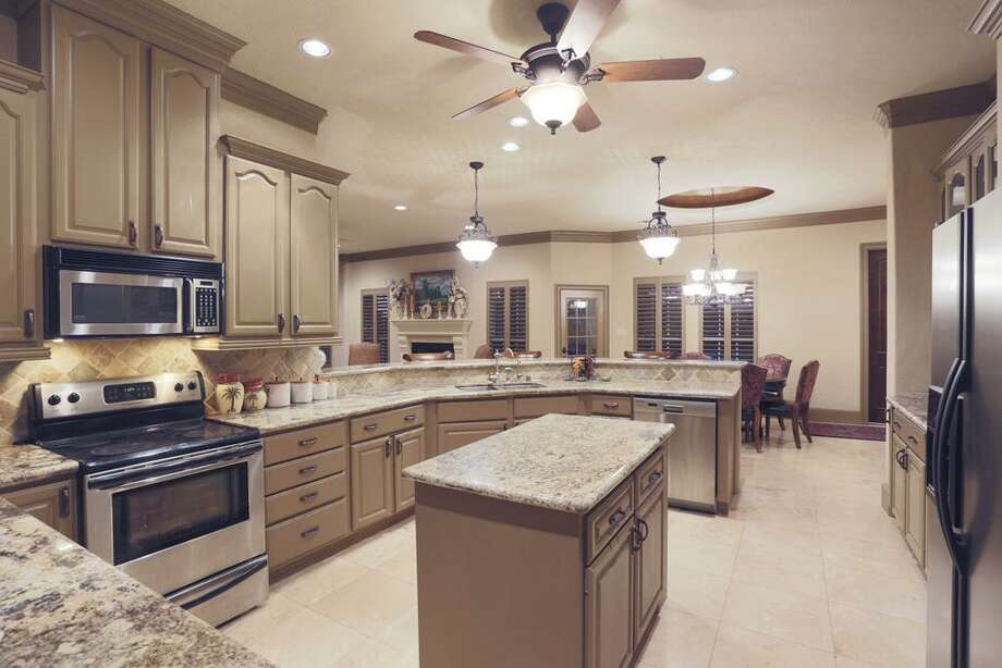 The inside view of the kitchen with plenty of counter space, granite counter tops and stainless steel appliances.
