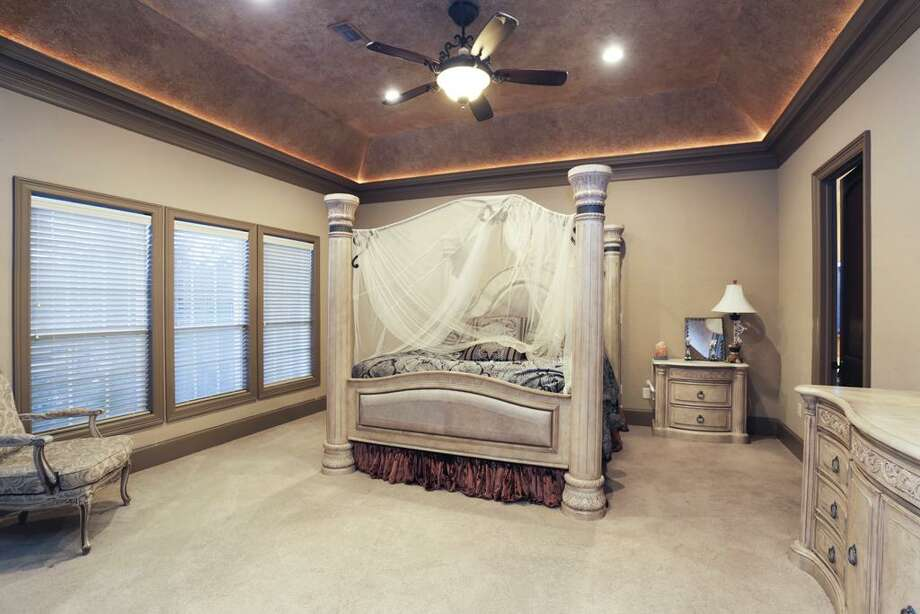 Master bedroom with magnificent hand crafted tray ceiling and a great view of the pool and acreage.