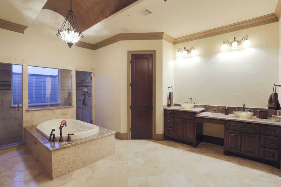 The Master Bath spotlights a large 7-head shower, whirlpool tub, separate sinks a men's room and separate lady's room with bidet highlighted by an arched ceiling and chandelier.