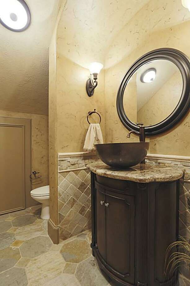 The hall bath features stone flooring, granite counters and stone imported from Italy.