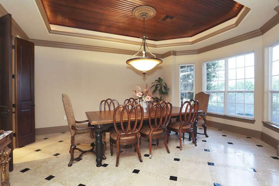 The formal dining room highlights the inset lighting, handcrafted woods and travertine flooring surrounded in marble and stone.